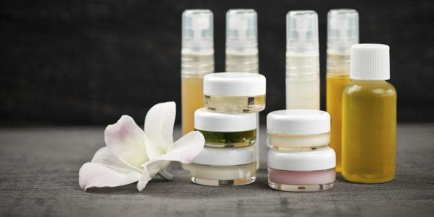 Various jars and bottles of skin care products with orchid