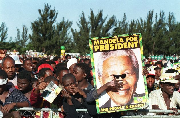 An ANC supporter at a rally in Durban 24 April 1994 holds a pair of sunglasses up to a Nelson Mandela...