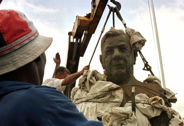 A man watches the bust of Hendrik Verwoerd being removed from the entrance of Pretoria's main