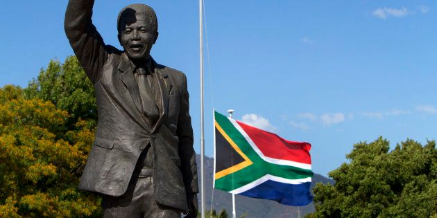 The South African flag flies at half mast behind the iconic Mandela statue at the entrance of the Groot...
