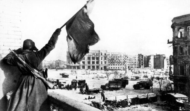 A soldier of the Red Army with the red flag after the German surrender at