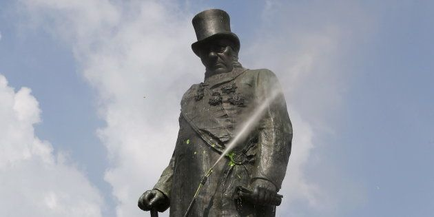 Municipal workers clean a statue of Paul Kruger after it was vandalized with paint a few days ago, in...