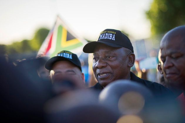Newly sworn-in South African president Cyril Ramaphosa (C) walks on an early morning from Guguletu township,...