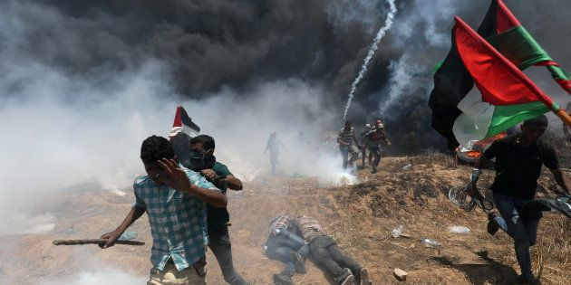 Palestinian demonstrators run for cover during a protest against U.S. embassy move to Jerusalem and ahead...