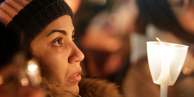 A woman becomes emotional during a vigil in support of the Muslim community in Montreal, Quebec, January...
