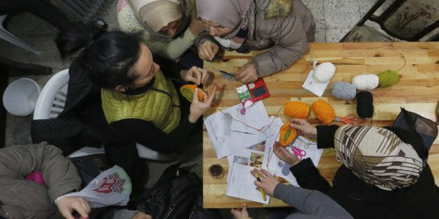 Syrian refugees attend a knitting lesson in
