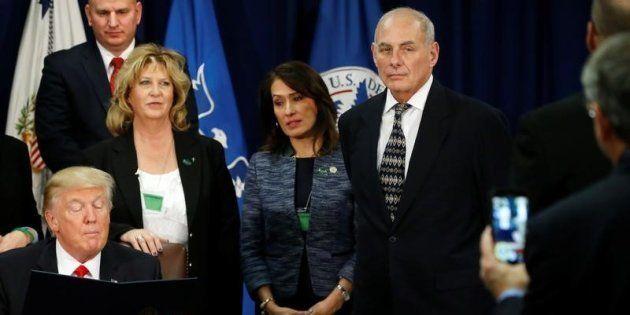 U.S. Homeland Security Secretary John Kelly (R) looks on as U.S. President Donald Trump signs an executive...