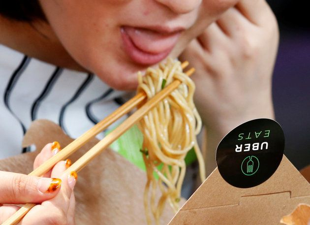A woman eats noodles during a demonstration of a food-delivery service at the launching event of UberEats...