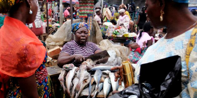 A woman sells fish at a street market in Lagos June 4,
