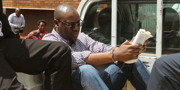 Zimbabwean pastor Evan Mawarire reads a bible, handcuffed, as he arrives at the Harare Magistrates court....