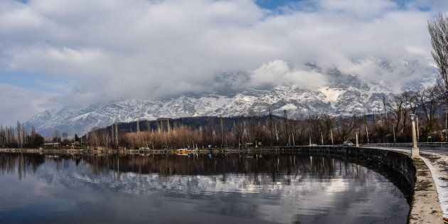 Shikara boats are moored the bank of Dal lake next to the snow clad mountains in Dal Lake on February...
