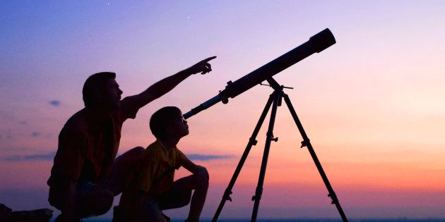 A young boy looking thru a telescope at sunset with his