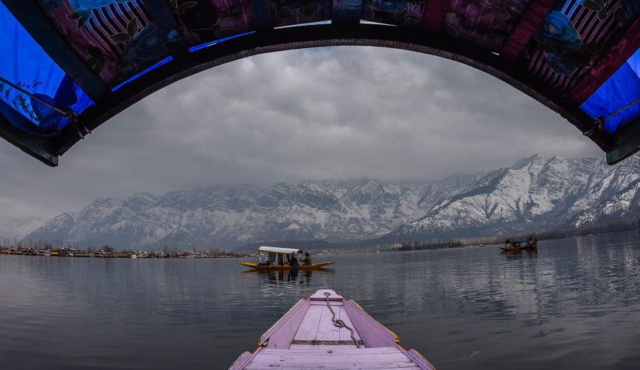 A Kashmiri boatman rows his boat next to the snow-capped mountains in Dal Lake on February 01, 2017 in...