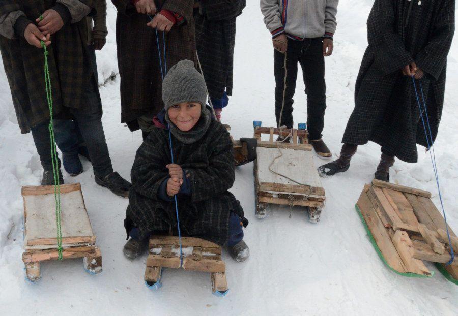 Kashmiri children enjoy sledge ride near Gund, about 80 kilometers (50 miles) north of Srinagar, on January...