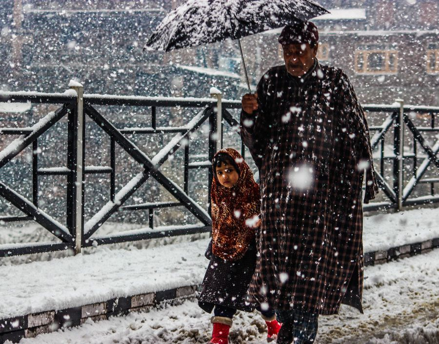 A man and his daughter seen making their way through heavy snowfall, on January 6, 2017 in Kashmir, India....