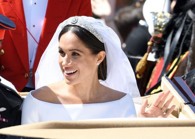 Meghan, Duchess of Sussex leaves Windsor Castle in the Ascot Landau carriage during a procession after...