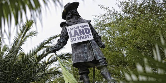 The statue of Jan van Riebeeck with a poster commenting on the debate about the removal of Cecil John...