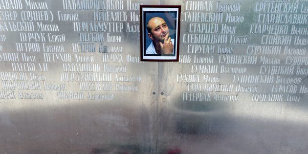 Flowers lie under a picture of 41-year-old anti-Kremlin reporter Arkady Babchenko on the memorial wall...