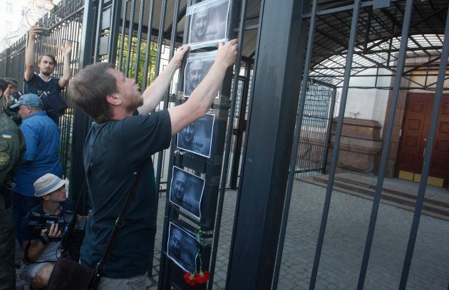 A man places the portraits of murdered journalist Arkady Babchenko on a fence of the Russian embassy...