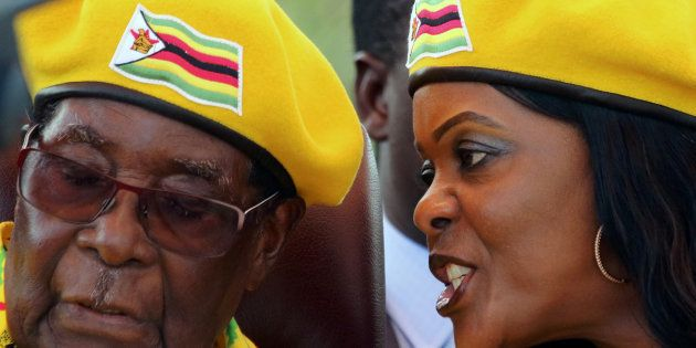 President Robert Mugabe listens to his wife Grace Mugabe at a rally of his ruling ZANU-PF party in Harare,...