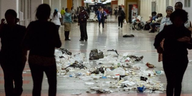 Patients walk through waste and garbage bags at the Charlotte Maxeke Hospital in Johannesburg, during...