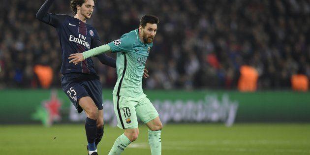 Paris Saint-Germain's French midfielder Adrien Rabiot (L) vies with Barcelona's Argentinian forward Lionel...