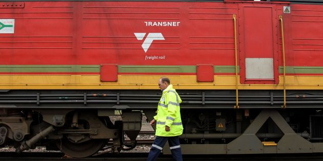 Jacobus van der Merwe, a train driver, passes a locomotive operated by Transnet at the company's rail...