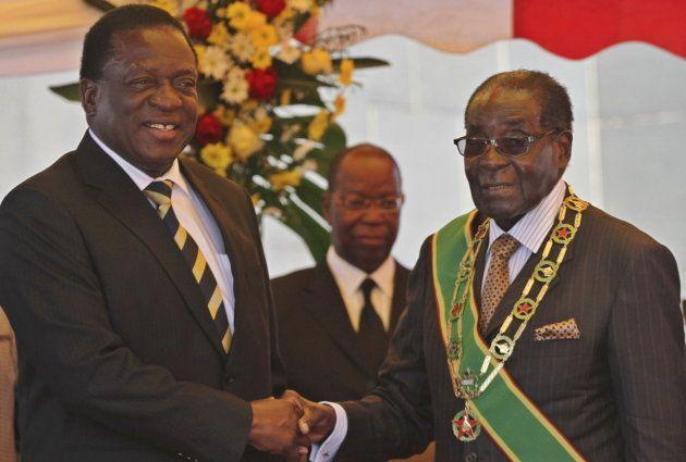 President Robert Mugabe (R) greets Vice President Emmerson Mnangagwa as he arrives for Zimbabwe's Heroes...