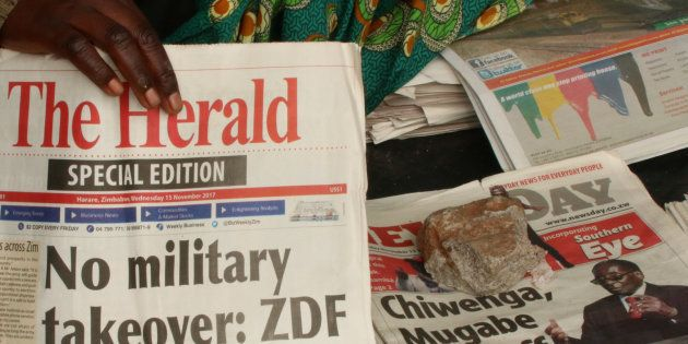 A vendor picks up a copy of a special edition of the state-owned daily newspaper The Herald in Harare,...