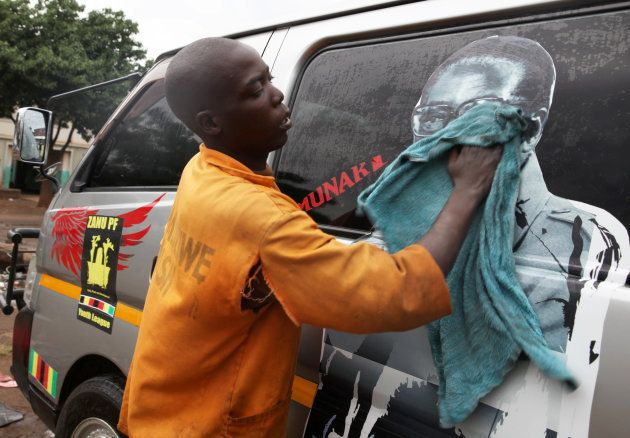 Youth washes a minibus adorned with picture of President Robert Mugabe at a bus terminus in Harare, Zimbabwe,...