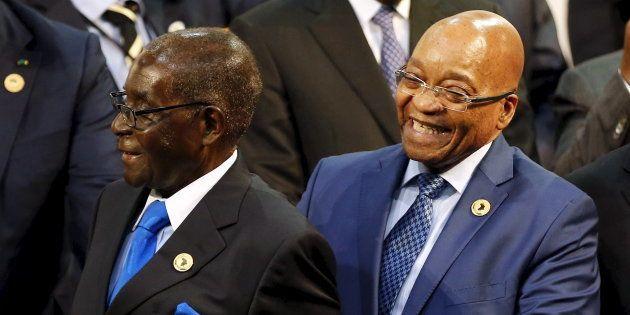 Zimbabwe President Robert Mugabe (L) reacts next to South Africa's President Jacob Zuma during the opening...