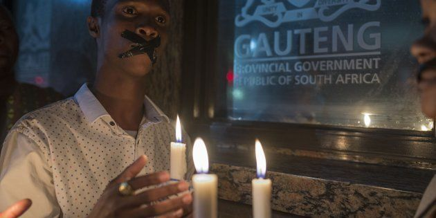 Demonstrators gathered in front of the office of the presidency of Gauteng State hold placards during...