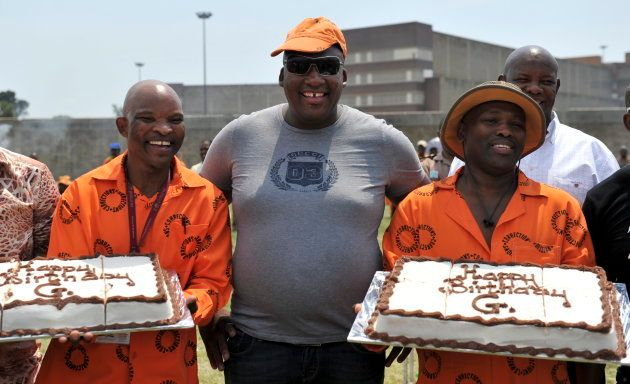 Controversial South African businessman, Gayton Mckenzie poses with his birthday cakes held by prison...
