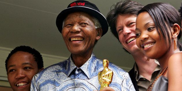 Former South African President Nelson Mandela (2nd L) poses with actor Presley Chweneyagae (L), actress...