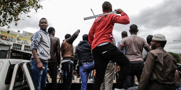 Somali migrants armed with rocks and sticks watch from the back of a pick up truck as a police helicopter...