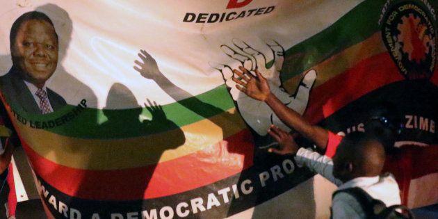 Zimbabweans celebrate next to a sign after President Robert Mugabe resigns in Harare, Zimbabwe November...