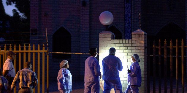 Police investigators collect evidence at a mosque where three men were attacked in Ottawa, South Africa,...