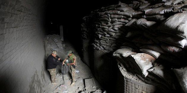Members of the rapid response forces inspect a tunnel was used by Islamic State militants as an underground...