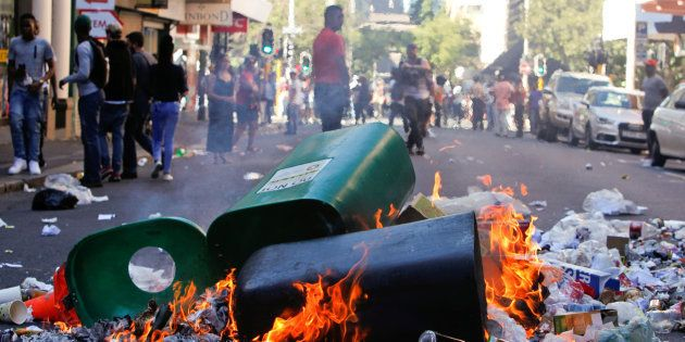 Rubbish burns after students protested outside the parliament during South African Finance Minister Pravin...