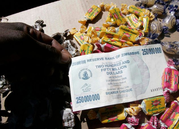 A sweet vendor holds a Zimbabwe $250-million note in the capital Harare May 10,