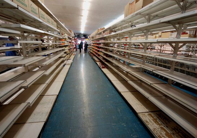 Shoppers walk along empty shelves inside a supermarket in Harare, July 11,