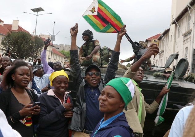 Protesters calling for Zimbabwean President Robert Mugabe to step down cheer in front of a military vehicle...