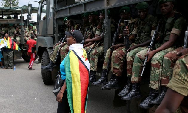 A local poses in front of the military truck after the swearing in of Zimbabwe's new president Emmerson...