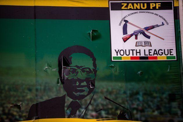 This photo taken on November 19, 2017 shows a vandalised billboard of Zimbabwe's president Robert Mugabe...