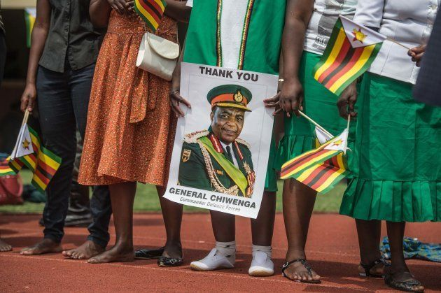 Supporters hold posters of Zimbabwe Army Chief of Staff General Constantino Chiwenga during newly sworn-in...