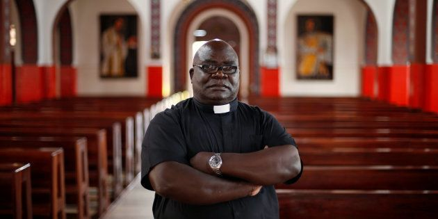 Father Fidelis Mukonori, a Jesuit priest who is Mugabe's close friend poses for a photograph after an...
