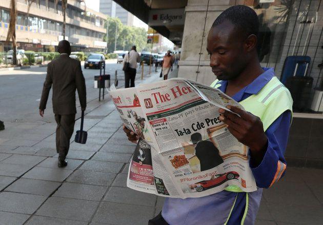 A Zimbabwean vendor reads a newspaper after President Robert Mugabe resigned in Harare, Zimbabwe, November...