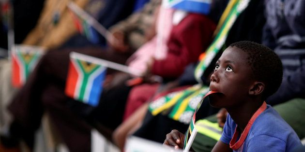 A boy holds a flag as South Africa's President Jacob Zuma addresses the National Youth Day commemoration,...