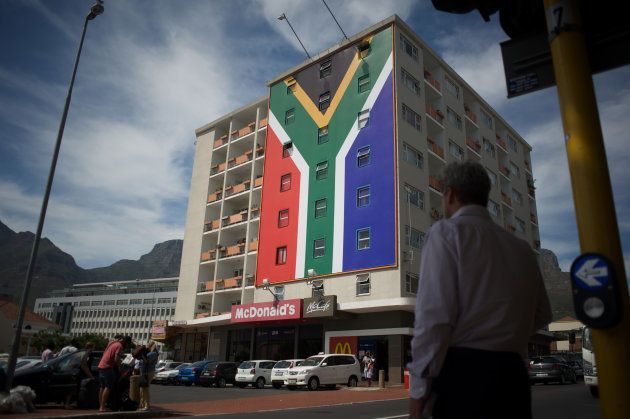 People walk past the billboard of the South African flag, newly set up on the building in the trendy...