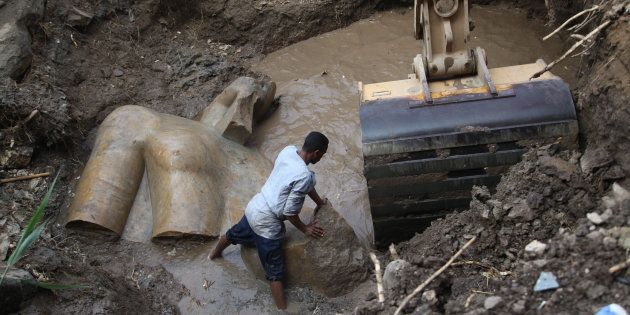 An Egyptian worker prepares to lift parts of a statue at the site of a new archeological discovery at...